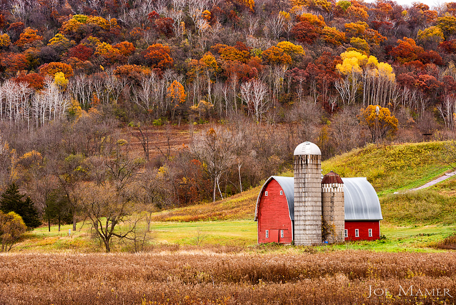 Red barn in colorful autumn valley.