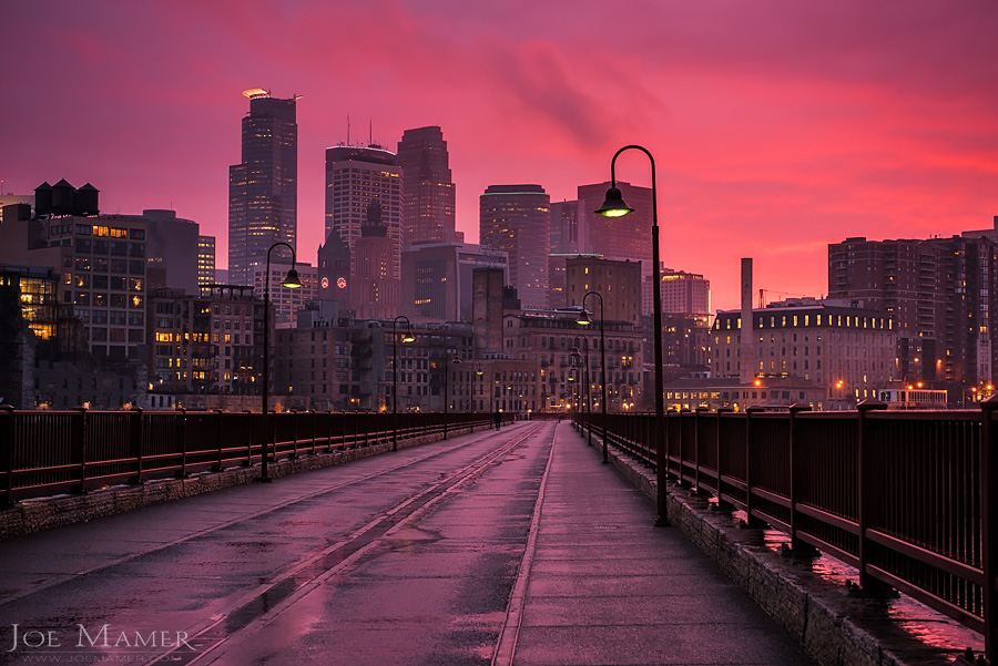 Minneapolis skyline from the Stone Arch Bridge as a rain storm breaks at sunset.